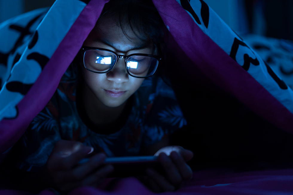 kids blue light glasses at night with mobile phone