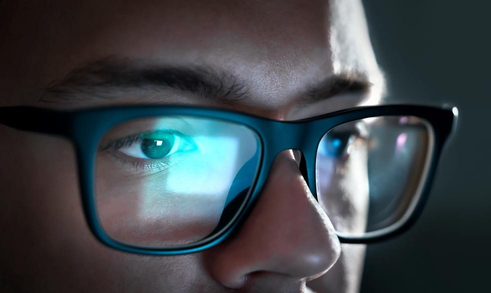 man at a computer wearing blue light blocking glasses